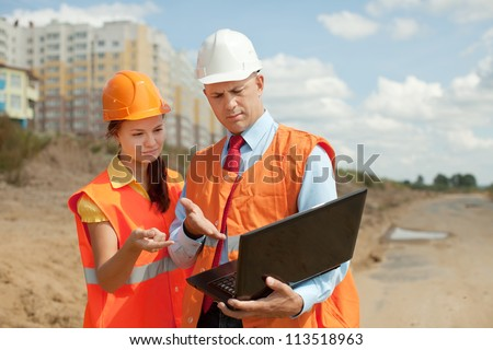 two builders wearing protective helmet works on the building site - stock photo