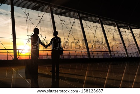 Two business man shake hand silhouettes city rendered with computer graphic. - stock photo