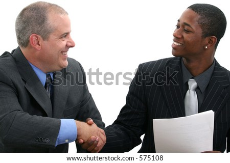 Two businessmen smiling and shaking hands. Shot in studio over white. - stock photo