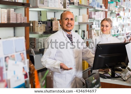 Two cheerful smiling pharmacists standing with a cash desk in the pharmacy - stock photo