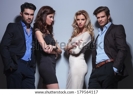 two elegant couples with the women holding their hands crossed and the man holding the hands in their pockets while looking into the camera; one woman is looking at the other man - stock photo