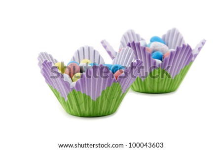 Two flower shaped baking cups filled with Easter candy - stock photo