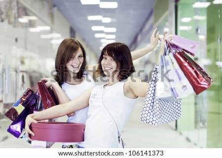 Two happy girls go with purchases - stock photo