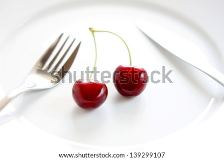 Two lush cherries on a white plate, with fork and knife. Dieting concept - stock photo