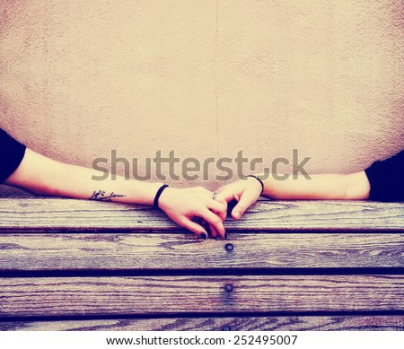 two people holding hands on a bench toned with a retro vintage instagram filter effect app or action - stock photo