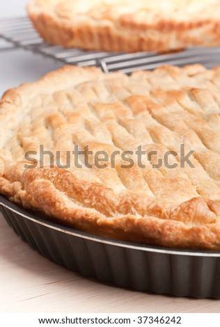 two pies - closed pie on a wooden board and open on a metal railing - stock photo