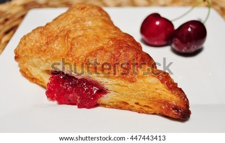 Two red cherries and delicious French pastry turnover filled with cherry jam, on a white dessert plate. - stock photo