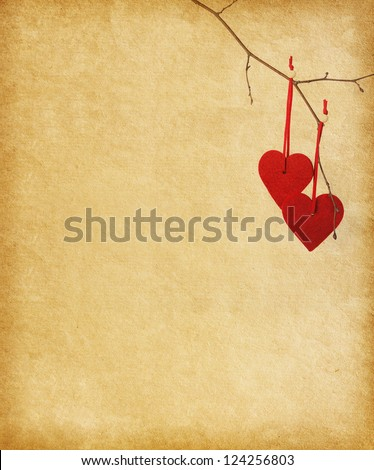 two red hearts, hanging on a branch over the paper background. - stock photo