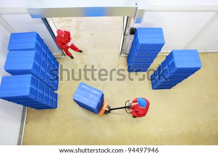 two workers preparing goods delivery in a small company warehouse - overhead view - stock photo