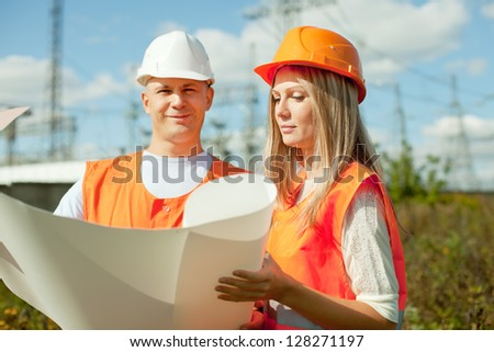 two workers wearing protective helmet works at electrical power station, Focus on woman - stock photo