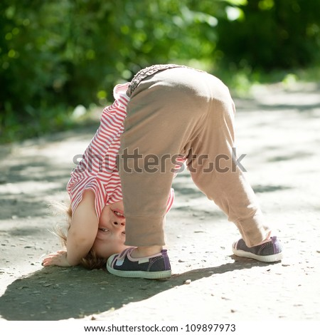 Two-year chid upside down in park - stock photo