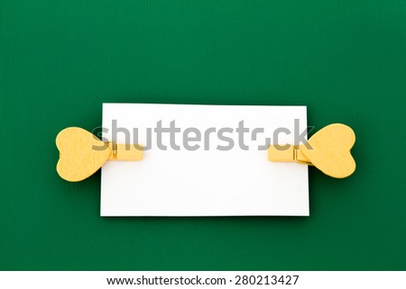 Two yellow wooden clothespins heart-shaped holding a white card on a green background - stock photo
