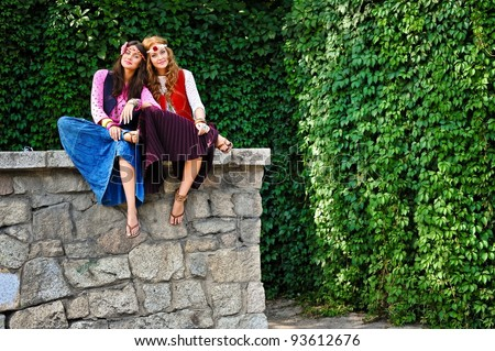 Two young beautiful girls of hippie sit in the street - stock photo