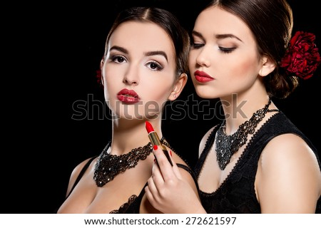 Two young beautiful women with stylish make-up and red lipstick in hand. Spanish women - stock photo