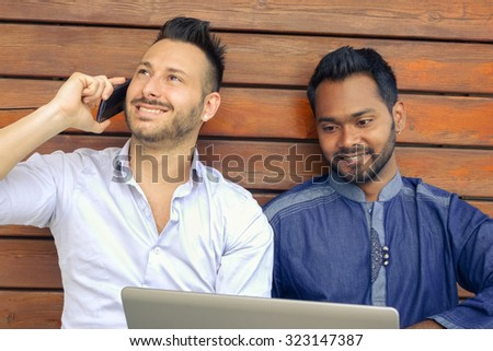 Two young hipster guys portrait using modern laptop and mobile phone - Happy businessmen with pc and smartphone - Indian and american man work outdoor - Multiracial friendship concept against racism - stock photo