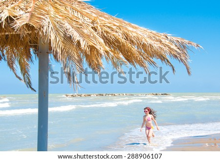 Umbrella on the beach and girl running in water - stock photo
