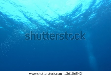 Underwater bubbles which raise from the depth of blue sea. - stock photo