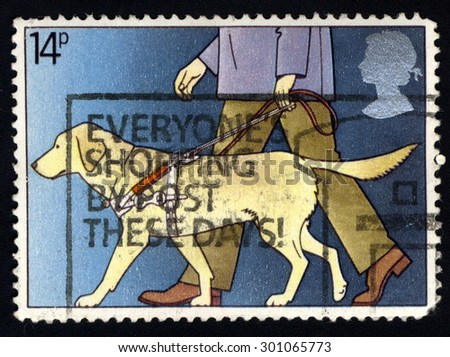 288 UNITED KINGDOM - CIRCA 1981: A stamp printed in the United Kingdom shows Blind Man with Guide Dog, circa 1981 - stock photo