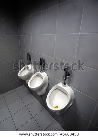 3 urinals in men's room  one was used recently  but didn't automatically flushed. - stock photo