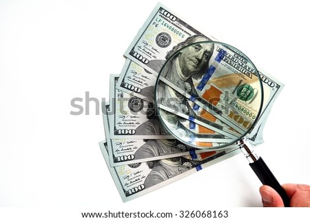 100 US Dollar banknotes under magnifying glass - stock photo
