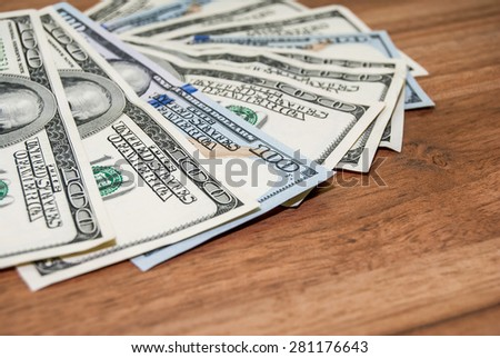100 US dollars banknotes on wooden background - stock photo