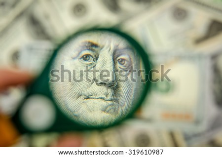 100 US dollars under a magnifying glass. close-up - stock photo