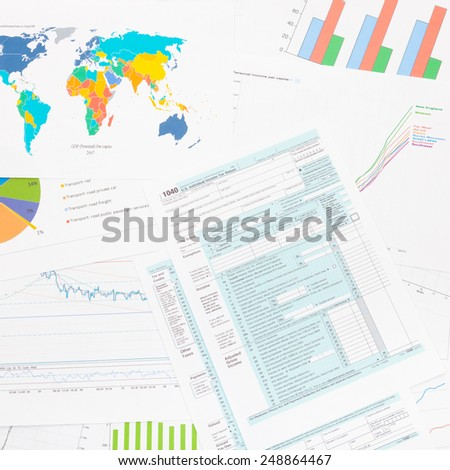 1040 US Tax Form with financial graphs on table - studio shot - stock photo