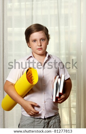 ?ute boy with books and yellow roll - stock photo