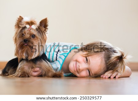 ��¡ute little girl playing with Yorkshire Terrier on the floor and smiling  - stock photo