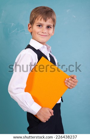 Ã?Â??ute schoolboy is holding an orange book against school blackboard - stock photo