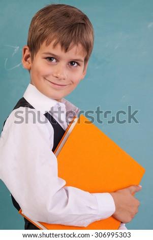 Ð¡ute schoolboy is holding an orange book against school blackboard - stock photo