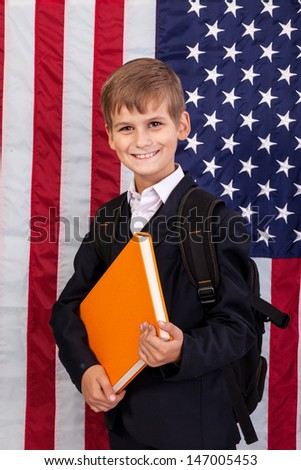 ������¡ute schoolboy is holding an orange book against USA flag - stock photo