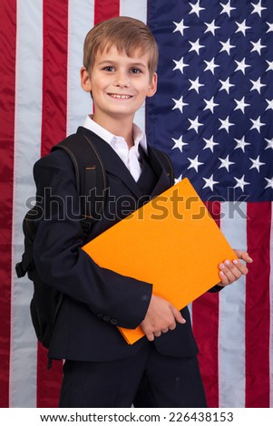 Ã?Â??ute schoolboy is holding an orange book against USA flag - stock photo