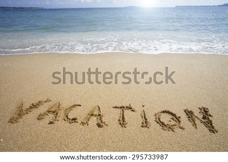 """""""Vacation"""" written in the sand on the beach with blue waves in the background - stock photo"""