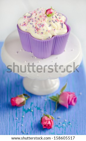 Vanilla cupcake with a rose on top of a blue wooden table - stock photo