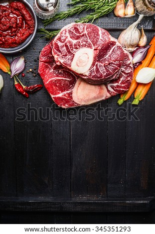 Veal shank slices meat and ingredients for Osso Buco cooking on dark wooden background,  top view, vertical border - stock photo