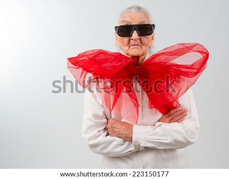 very old lady witha  huge red bow and  eyeglasses - stock photo