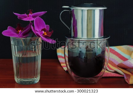Vietnamese coffee and orchid on black background - stock photo