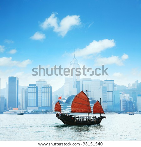 view of Hong Kong's Vicotria harbor with one chinese boat through the river - stock photo