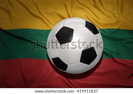vintage black and white football ball on the national flag of lithuania - stock photo