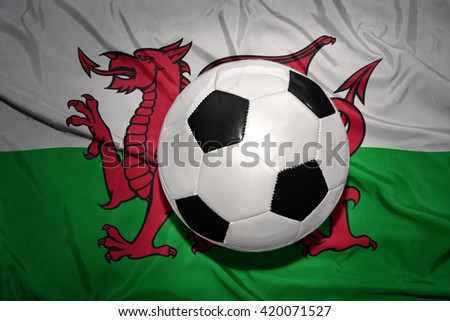 vintage black and white football ball on the national flag of wales - stock photo
