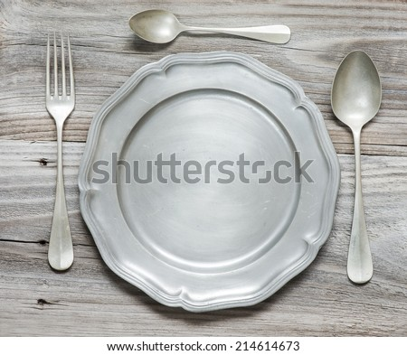 Vintage fork, spoons and pewter plate on old wooden boards - stock photo
