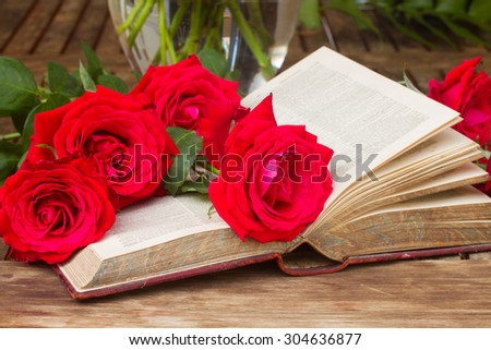 vintage old book  on table with fresh red roses - stock photo
