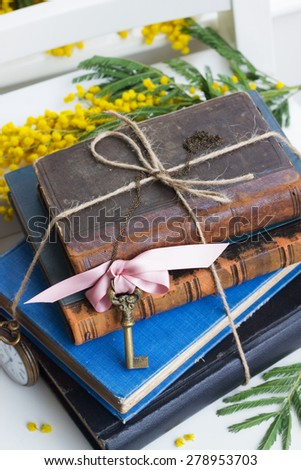 vintage old books  with key and french mimosa flowers - stock photo