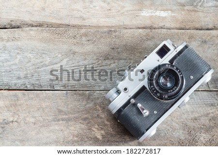 Vintage photo camera on a wooden table - stock photo