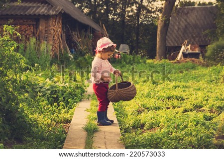 vintage portrait of Cute kid with big basket having fun at countryside - stock photo