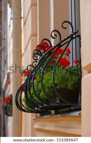 Vintage wrought iron flower box holder under window - stock photo