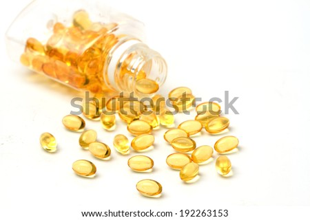 vitamin capsules with  E poured out of bottle - stock photo