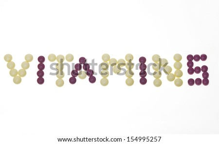 """Vitamins"" text written with pills - stock photo"