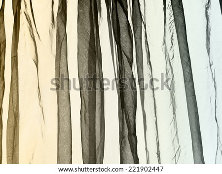 Voile curtain fading colors yellow to grey to blue background   - stock photo
